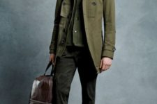 With olive green cardigan, trousers, brown shoes and big brown bag