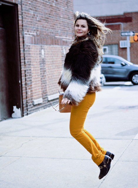 With orange pants, black boots and brown clutch