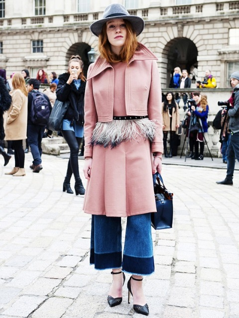With pink coat, black pumps and blue small bag