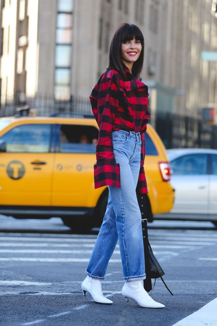 With plaid shirt, cuffed jeans and black bag