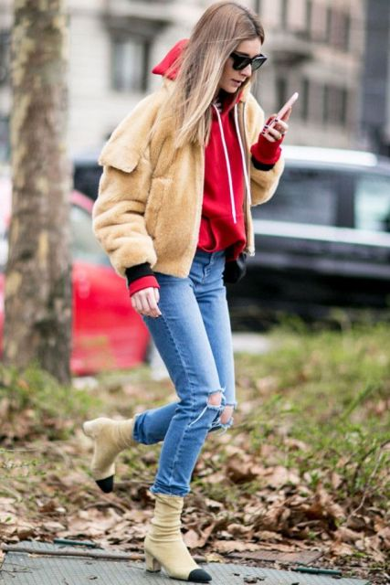 With red sweatshirt, distressed jeans and two color boots
