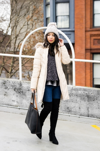 With sweater, skinny jeans, black high boots, black bag and beanie