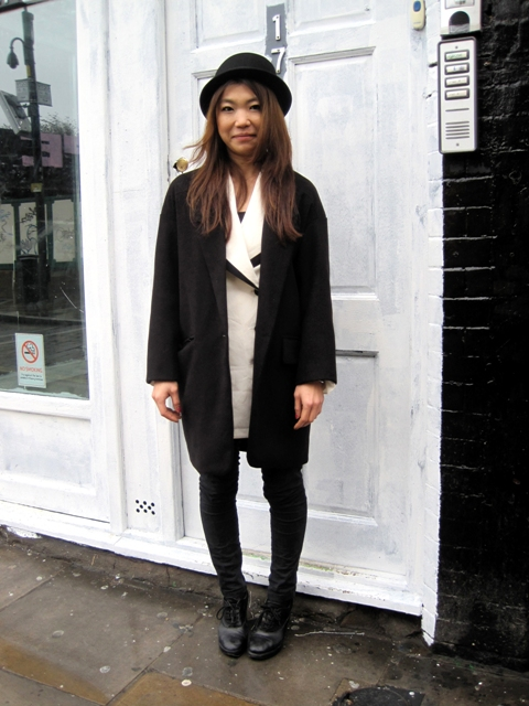 With white cardigan, black coat, skinny pants and boots