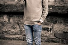 With white shirt, beige sweater, jeans and sneakers