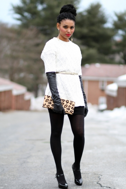With white sweater, mini skirt, white belt, printed clutch and pumps