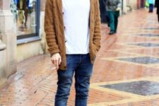 With white t-shirt, jeans, brown boots and brown cardigan