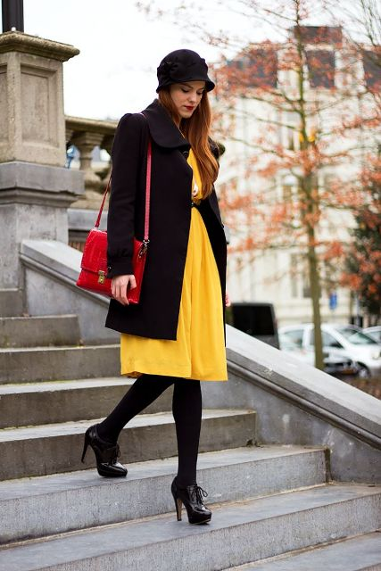 With yellow knee-length dress, black coat, black tights, ankle boots and red bag