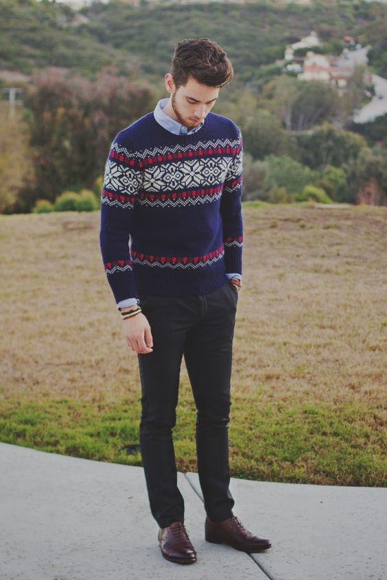 black pants, brown shoes, a blue shirt and a printed navy sweater