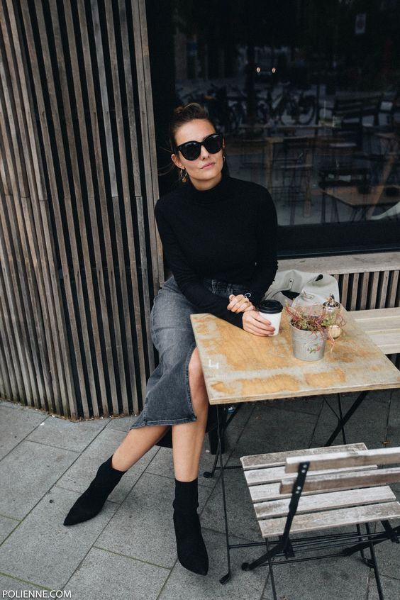 a black denim midi skirt, a black sweater, black suede sock boots