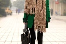 03 an emerald coat, a beige scarf with two pockets over it and black boots