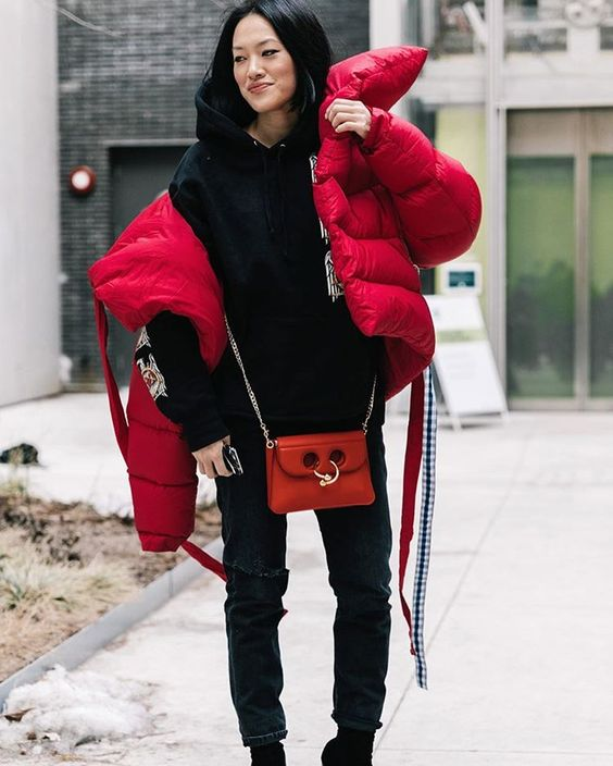 an oversized red puffer jacket worn with jeans and a hoodie for a comfy winter look