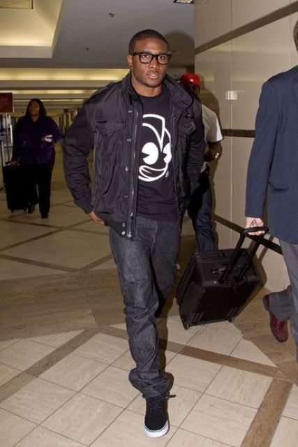 black jeans, a black printed sweatshirt, a black puffer jacket and sneakers