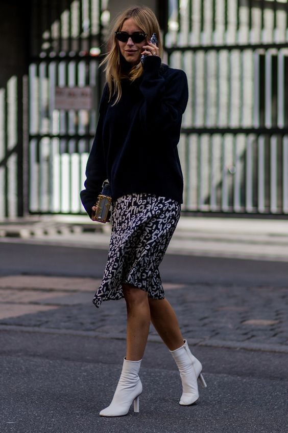 a navy oversized sweater, a printed knee skirt and white sock boots
