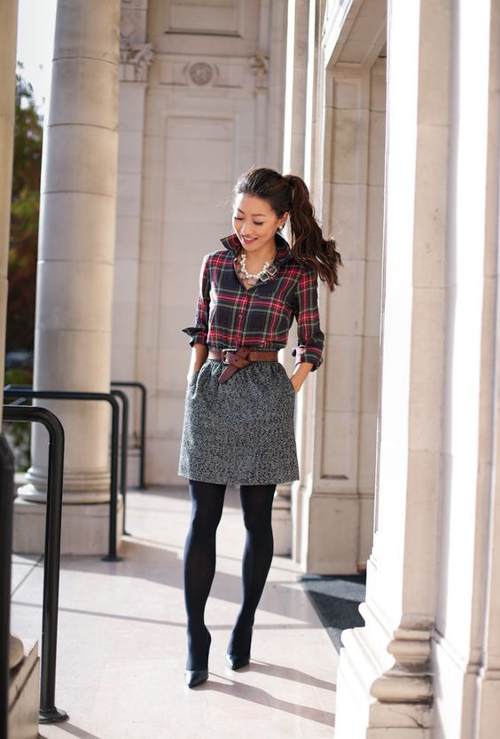 a plaid shirt, a tweed skirt, black tights and black shoes, a leather belt