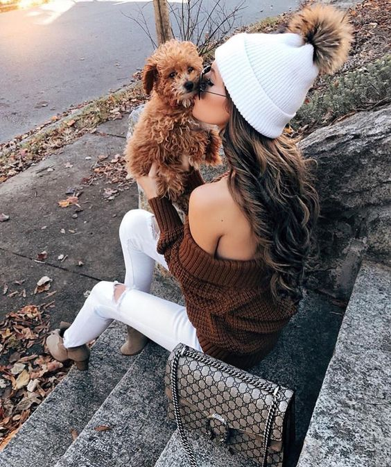 a white beanie with a brown faux fur pompom and a brown off the shoulder sweater