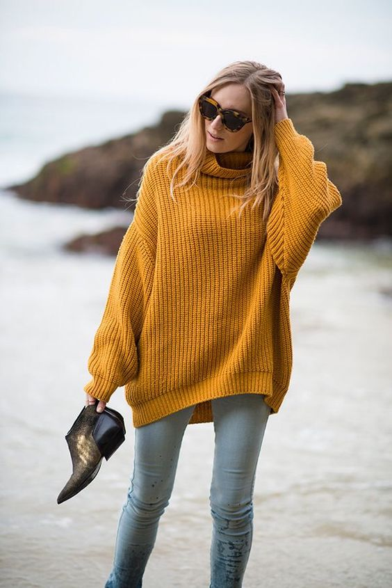 a mustard chunky knit sweater, light blue jeans and booties