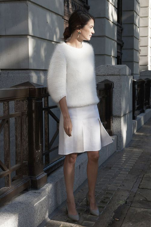 a white anogra sweater with half sleeves, a white pleated skirt and grey heels for a modern look