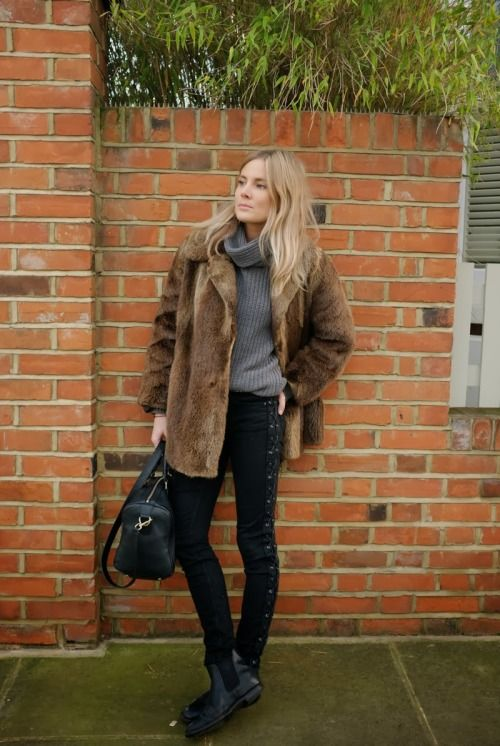 black jeans, a grey sweater, a faux fur coat and black chelsea boots