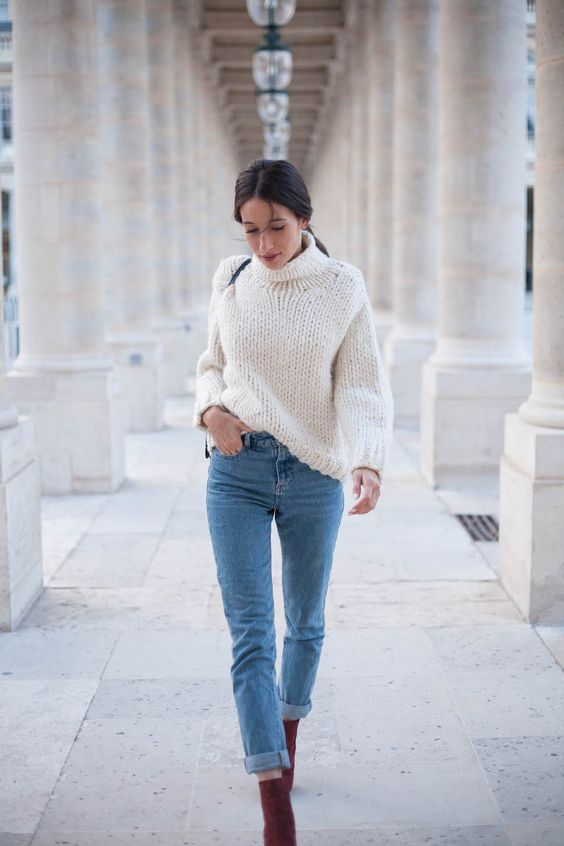 a white chunky knit sweater, blue jeans and burgundy suede booties