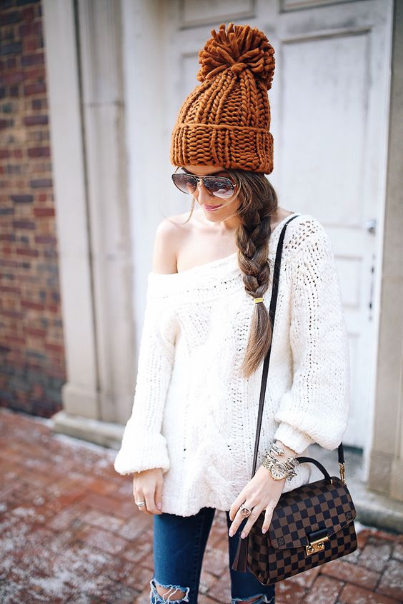 a large messy braid and a chunky knit beanie is a perfect match
