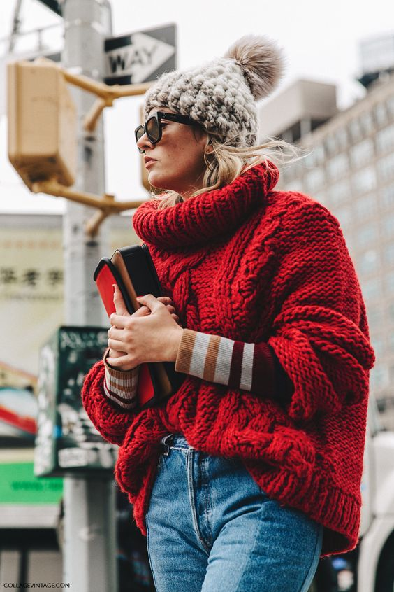 an oversized red chunky knit sweater with blue jeans and a chunky knit beanie