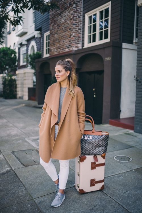 white jeans, a grey tee, a camel coat and grey trainers for a comfy look