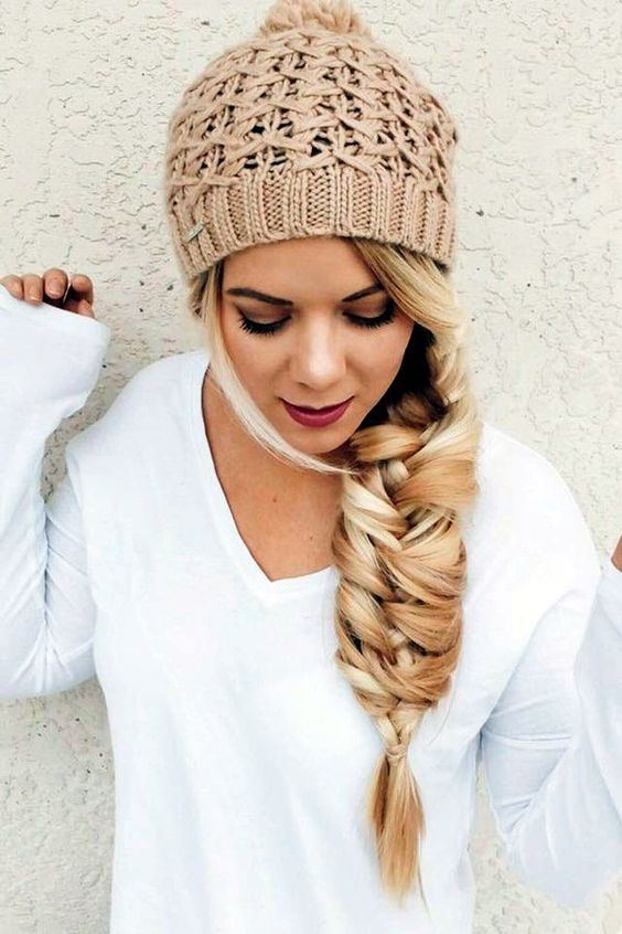 a large twisted fishtail braid and a neutral beanie look glam together