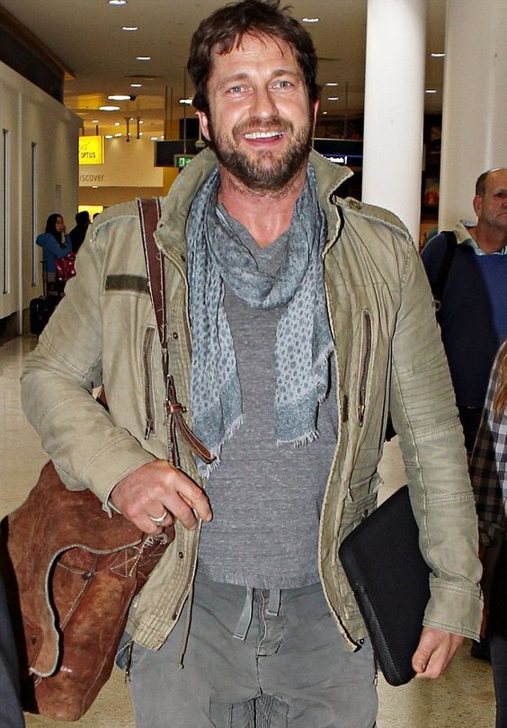 grey pants, a grey sweatshirt, a grey scarf and an olive green leather jacket