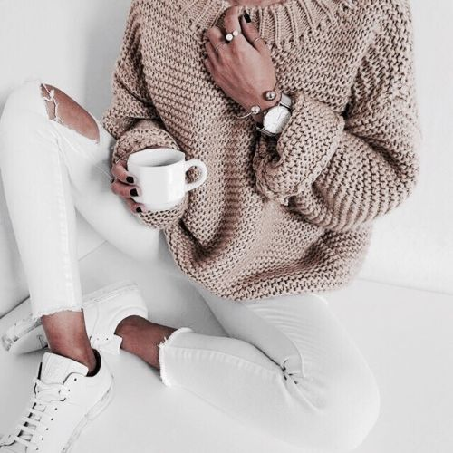 white ripped jeans, white sneakers and a beige chunky knit sweater