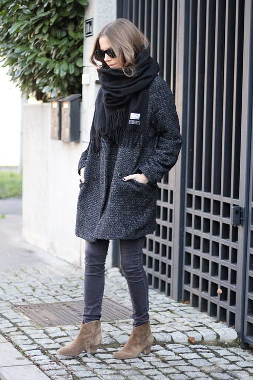 a black coat, a black scarf, grey jeans and light brown booties
