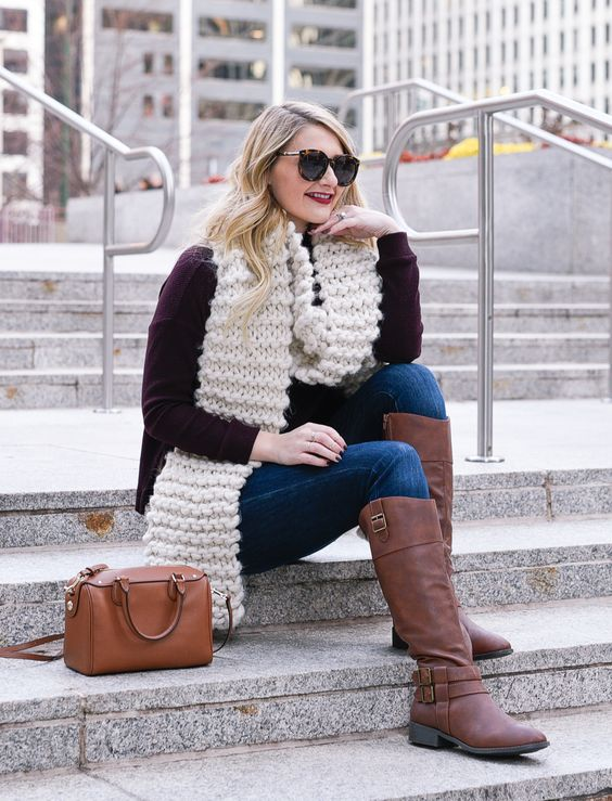 a burgundy sweater, a creamy chukny knit scarf, navy jeans and brown boots