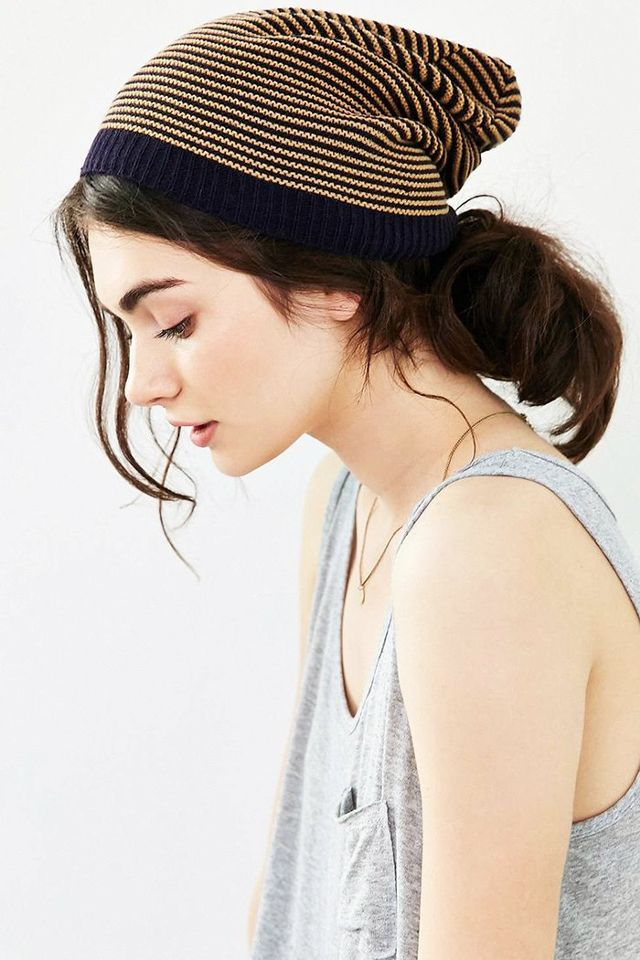 a messy low bun with bangs and a striped beanie for an effortlessly chic look