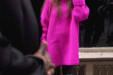 12 a neon pink chunky knit long sweater, black leather pants and boots and a black beanie
