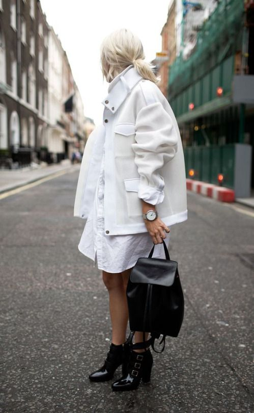 a white shirt dress, a white coat and black boots and a backpack for a contrast