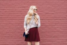 13 a neutral turtleneck sweater, a burgundy pleated mini skirt, grey flat suede tall boots