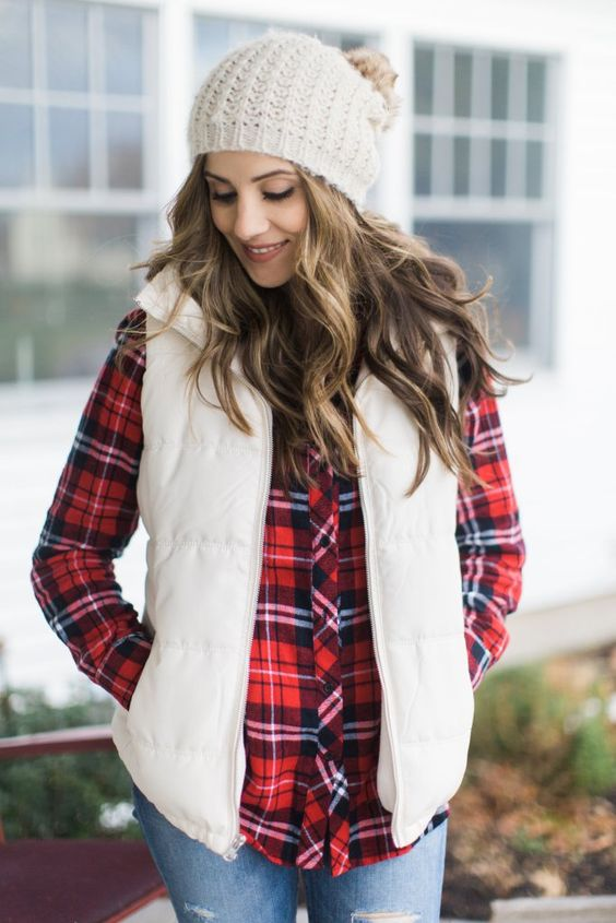 blue jeans, a plaid shirt, a creamy puffer vest and a creamy beanie