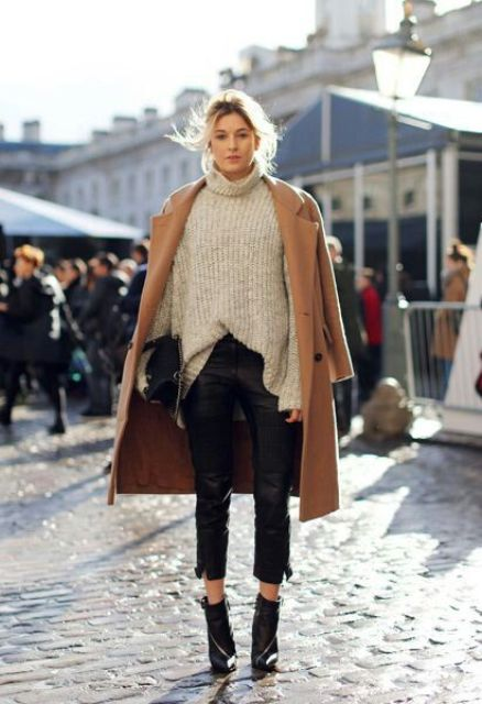 a neutral chunky knit sweater, black cropped pants, black boots and a camel coat