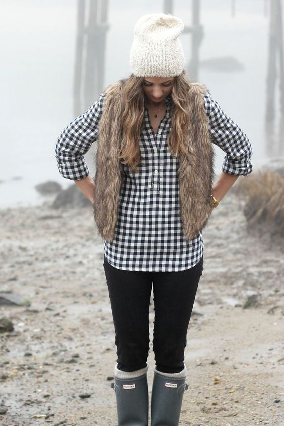 black jeans, a plaid shirt, a faux fur vest, a white beanie and grey boots