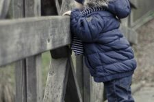 15 a navy puffer jacket with grey faux fur and a navy beanie for a stylish boy toddler look