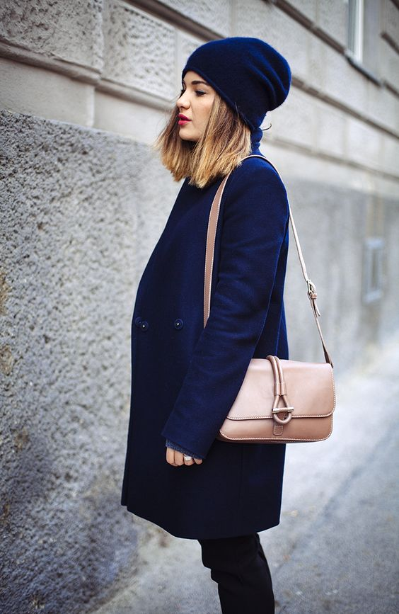 a navy sleek beanie that matches the coat and a contrasting bag