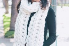 15 a white chunky knit scarf over a black sweater and blue jeans