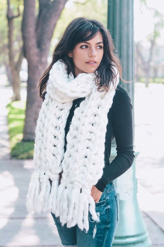 Picture Of A White Chunky Knit Scarf Over A Black Sweater And Blue Jeans
