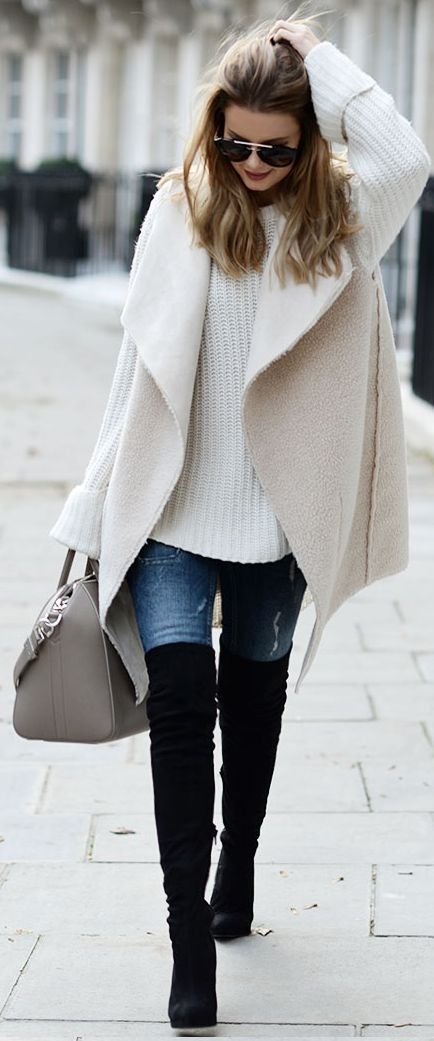 a work-appropriate layered fall look with a white chunky knit sweater, a matching sleeveless coat, blue jeans and black tall boots