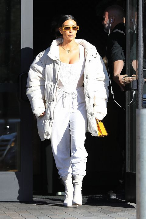 Kim Kardashian wearing a monochrome outfit with a white puffer coat looks chic