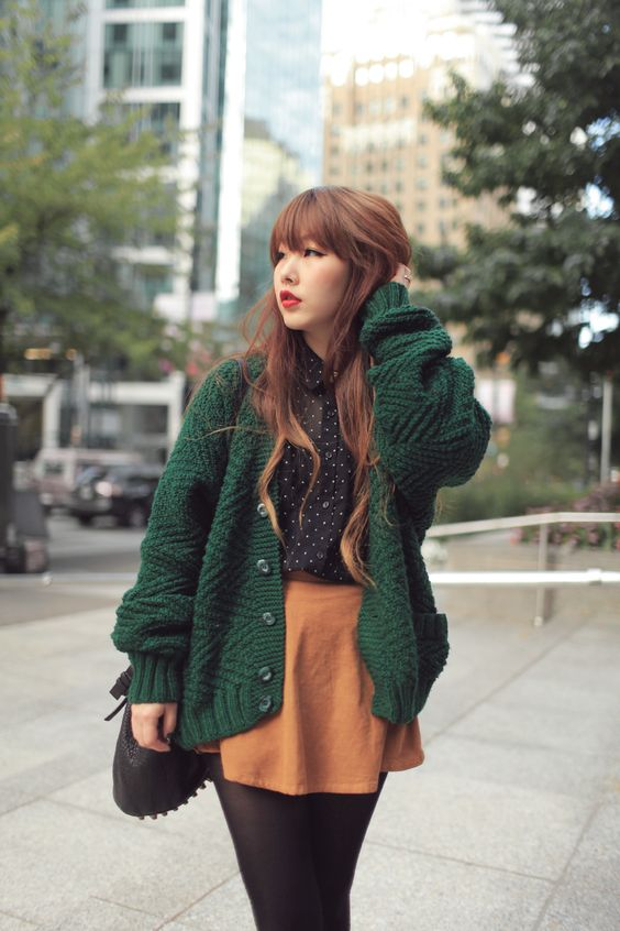 an orange mini skirt, a polka dot black shirt, an emerald cardigan for a cute look