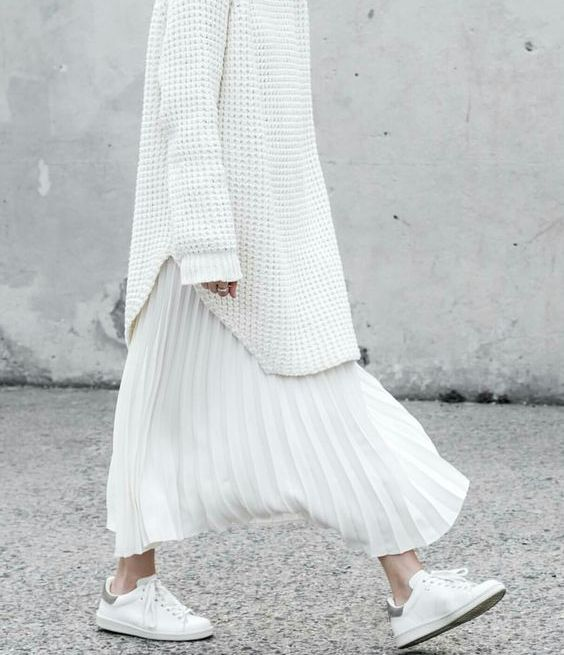 an oversized white sweater, a white pleated maxi skirt and white sneakers to feel comfy