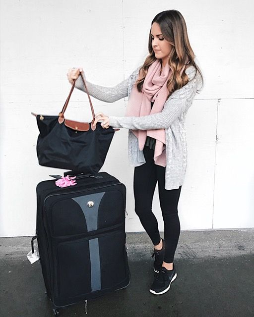 black leggings, a tee, a pink scarf, black sneakers and a grey cardigan is a comfy look for travelling