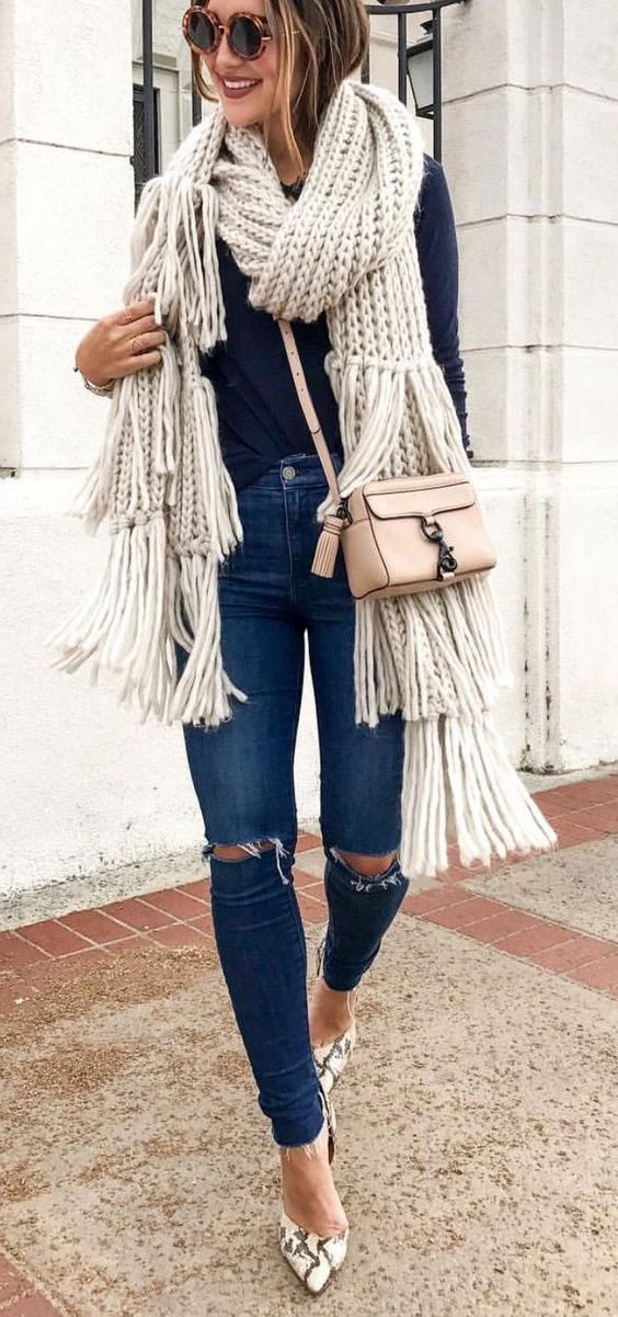 ripped jeans, a navy shirt, a neutral chunky knit scarf with tassels and snake print shoes