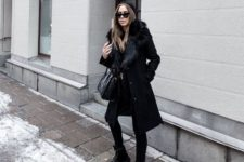 Black coat with fur, skinny pants, lace up boots, bag and beanie