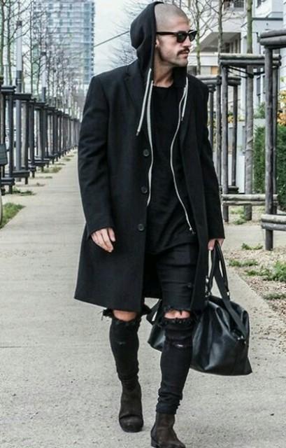 Black hoodie, knee-length coat, distressed pants, suede boots and bag